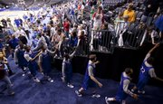 The Kansas Jayhawks slap hands with fans as they leave the court following practice at the Ford Center in Oklahoma City, Wednesday, March 17, 2010.