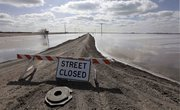 A road is closed because of overland flooding from the Sheyenne River on Saturday in West Fargo, N.D. Forecasters lowered their flood crest predictions a foot lower than anticipated for the area expecting the Red River in Fargo to crest today.
