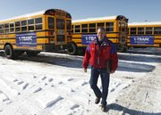 Marc Horner, fleet manager for Jefferson County public schools in Lakewood, Colo., walks near school buses with advertisements on their sides at the school's bus maintenance facility. Several states allow advertising on school buses, including Colorado, Arizona, Florida, Minnesota, Tennessee and Texas.