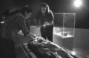 """Jennifer Ring, center, and Hu Guizhen examine the Beauty of Xiaohe, a 3,800-year-old mummy discovered in the Tarim Basin in far western China, at the """"Secrets of the Silk Road: Mystery Mummies from China"""" exhibit at the Bowers Museum in Santa Ana, Calif. The exhibit opened Saturday."""