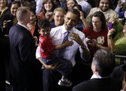 President Barack Obama picks up 4-year-old Barack Anthony Stroud after speaking about health care reform, Thursday at the University of Iowa in Iowa City.