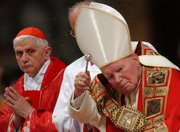 In this file photo taken Sept. 11, 2002, then-Cardinal Joseph Ratzinger of Germany, left, now Pope Benedict XVI, is seen with late Pope John Paul II during Mass in St. Peter's Basilica at the Vatican. The Vatican is facing one of its gravest crises of modern times as sex abuse scandals move ever closer to former Benedict — threatening not only his own legacy but also that of his revered predecessor.