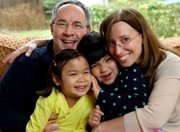 Bethany and Kevin Durkin hold their daughters Olivia, 7, left, and Lucy, 5, March 13 in their in Katonah, N.Y,. home. The Durkins are part of a growing number of parents who have adopted special-needs children from China. Olivia had a weak, underused right arm when she was adopted in 2004, while Lucy had a cleft palate that was repaired through surgery soon after her adoption in November 2007.