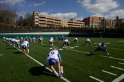 Offensive players on Kansas University's football team stretch prior to the Jayhawks' first practice Sunday on the KU practice fields. After having worked out twice without pads, the Jayhawks will don pads today for the first time this spring.