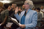 Eileen Roddy, right, raises her hand during the oath of allegiance during the ceremony for Naturalization for new citizens at the U.S. District Court  Mar. 26, 2010 in Kansas City, Kan.