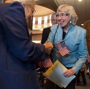 Eileen Roddy, right, of Lawrence, gets an American flag from Angie Solomon on March 26 following the naturalization ceremony for new U.S. citizens at the U.S. District Court in Kansas City, Kan. Roddy came to the U.S. from Northern Ireland. Solomon is an auxiliary member of Wyandotte American Legion Post 83.