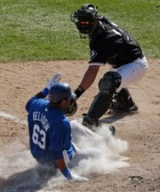 Kansas City's Edwin Bellorin, left, scores ahead of the tag of White Sox catcher Jared Price in the eighth inning. The Royals won, 10-8, Sunday in Glendale, Ariz.