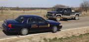 Kansas Highway Patrol troopers inspect a black truck on Tuesday after the troopers and Douglas County Sheriff deputies helped Shawnee County deputies apprehend a suspect who led the officers on a half-hour in western Douglas County. The suspect was taken into custody.