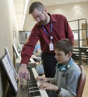 Central Junior High music teacher Kevin Hart helps eighth-grader Bryan Bourdon during a music explorations class Tuesday. Hart was given a teacher innovation grant by the Lawrence Schools Foundation. Hart has proposed that a piece of music be written about the World War I soldiers from Lawrence to whom Liberty Memorial High School was dedicated. Liberty Memorial is now Central.