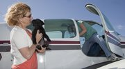 Rhonda Schademann, Perry, says goodbye to one of eight puppies she fostered before their flight out of the Lawrence airport Wednesday.