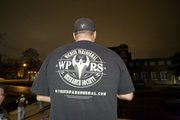 Shane Elliott, founder of the Wichita Paranormal Research Society, wearing a WPRS T-shirt, stands outside the theater.