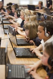 Corpus Christi third-grader Rylie Occhipinto leans into her computer screen as she and surrounding classmates work in Jason Dolan's technology class.