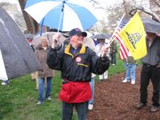 Ed Williams, a volunteer for the Tea Party Express, trades flags for donations at the rally Friday on the Statehouse grounds.