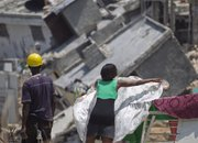 People stand in front of the rubble of collapsed buildings Saturday in Port-au-Prince. A large-scale cleanup is just beginning to tackle piles of rubble from the magnitude-7 quake, which generated 20 million to 25 million cubic yards of debris.