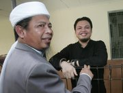 Muhammad Jibriel, right, who was on trial in Jakarta, Indonesia, on charges of helping fund last year's twin suicide bombings at luxury hotels in Jakarta, speaks with his father, Abu Jibriel, in this March 25 photo. The elder Jibriel is a cleric accused by the U.S. of being a key leader in Jemaah Islamiyah, Southeast Asia's main extremist network.
