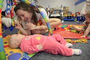 Child Care worker Jessica Soerries, 22, gives a little special attention to Lillian Poteete at Stepping Stones, 1100 Wakarusa Drive.