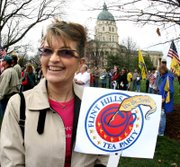 "In this April 2, 2010 photo, Gail Lortscher, Manhattan, Kan., a participant in the Tea Party Express national bus tour smiles as she holds a sign on the grounds of the Statehouse in Topeka, Kan. Lortscher, a Sarah Palin look-alike, says, ""I can't even go into a McDonald's without people yelling at me, 'Hey, Sarah. """