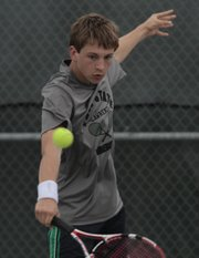 Free State's Patrick Carttar returns a serve against Shawnee Mission North. The Firebirds played for less than an hour on Tuesday at Free State High before rain canceled the match.