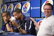 Kansas head coach Bill Self pats Xavier Henry on the back after handing him a tissue during a press conference in which Henry declared his intention to enter the NBA draft, Wednesday, April 7, 2010 at Allen Fieldhouse. C.J. Henry, at left, supported his brother at the podium.