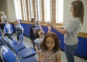 Essy Sonora, center, slaps a high-five with Erin Atwood, Kansas University sophomore, Topeka, during a game of musical chairs Thursday at KU's Burge Union. Atwood is a co-coordinator of Into the Streets, a KU community volunteer program.