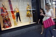 Shoppers walk past the the Oscar de la Renta display at the Saks Fifth Ave. retail store Thursday in New York. Luxury retailer Saks Inc.'s sales at stores open at least a year grew 12.7 percent in March, lifted by strong results in women's designer clothing, handbags, men's clothing and accessories.
