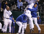 Kansas City's Willie Bloomquist (8) celebrates with Mitch Maier, right, Brayan Pena, center, and Jason Kendall (18) after Bloomquist scores the game-winning run. The Royals won, 3-2 in 11 innings, on Wednesday in Kansas City, Mo.