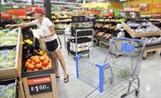 Lawrence resident Andrea Baloga grabs a couple of limes from the rack in the produce section at Wal-Mart in northwest Lawrence. Store manager Ryan Edwards said things were going well at the store and that it had shown to be a very good convenience for customers.