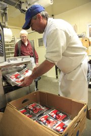 Tom Pyle, left, watches his son Tom Pyle Jr. package some of the last beef jerky Thursday at Pyle Meat Co. in Eudora. The company was in business for 50 years but is closing its doors as a result of the recession.
