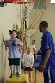 Third-grader Nolan Smith smiles when it's his turn to try to dunk on Markieff Morris. Members of the KU men's basketball team took some time Wednesday to help students at Sunflower Elementary learn about fun and fitness.