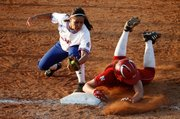 A Nebraska baserunner slides safely under the tag of KU's Sara Ramirez during the game Wednesday, April 14, 2010. The Jayhawks lost 2-0 to the 'Huskers and fell to 1-8 in Big 12 Conference play.