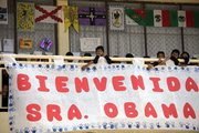 """Students at Siete de Enero primary school stand behind a banner welcoming first lady Michelle Obama on Wednesday to their school in a low-income neighborhood of Mexico City. The sign reads in Spanish """"Welcome Mrs. Obama."""""""