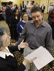 Brad Steele, right, interviews with Betsy Harris, of Express Employment Professionals, at a National Career Fair on Thursday in Cincinnati. The number of newly laid off people signing up for unemployment benefits rose sharply for the second straight week, suggesting that jobs are still hard to come by even as the economic recovery gains traction.