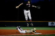 Lawrence High first baseman Aaron Gile leaps over a Topeka Hayden runner while trying to pull down a high throw. The Lions lost, 7-5, in 12 innings on Friday at Lawrence High.