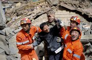A survivor waves after he was rescued Thursday from rubble of a collapsed building after an earthquake Wednesday in Yushu county, western China's Qinghai province. China poured rescue crews and equipment into a mountainous Tibetan region Thursday in a bid to find survivors more than a day after strong earthquakes killed more than 700 people and injured thousands.