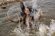 A nomadic Gujjar girl plays in the River Tawi to get respite from the heat Friday in Jammu, India. Last month was the warmest March on record worldwide, based on records back to 1880, scientists reported Thursday.