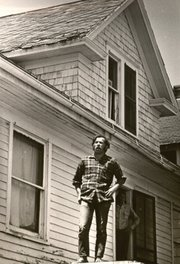 A man stands on the roof of a house along Oread Avenue, a hot spot for civil unrest during the summer of 1970.