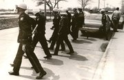Police with riot gear walk toward the Lawrence High School, a scene of frequent violence between white and black students during the spring of 1970.
