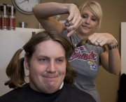 Kansas football lineman Brad Thorson grimaces as Tisha Cobb cuts the first lock of his hair Saturday at Tisha Cobb Hair Design. Thorson is donating the long locks to Pantene Beautiful Lengths for cancer patient wigs.