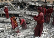 Tibetan monks help dig Friday to search for students believed to be trapped at a collapsed school after an earthquake in Yushu County, northwest China's Qinghai province. Rescuers probed the rubble for sounds or movement Friday in a rush to find anyone buried alive more than 48 hours after an earthquake hit western China, killing hundreds of people.