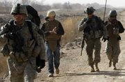 Associated Press reporter Chris Torchia takes notes as he walks with U.S. soldiers of the 4th Battalion, 23rd Infantry Regiment, 5th Brigade, 2nd Infantry Division during a dismounted patrol Feb. 15 in the Badula Qulp area, west of Lashkar Gah in Helmand province, southern Afghanistan.