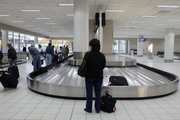 A woman waits for her luggage in the east terminal at Lambert St. Louis International Airport. Most carriers now charge around $25 for the first checked bag and $30 for a second bag. The airlines have size and weight requirements, too.