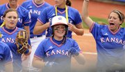 KU sophomore Marissa Ingle (21) is all smiles with teammates after cracking a homerun and scoring two as the KU women hosted the Okahloma State cowgirls on Sunday April 18, 2010. Kansas fell 4-3 in a hard-fought game.