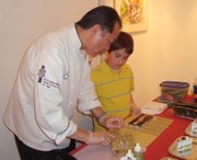 Chef Instructor Tatsu Miyazaki  shows Trevor Arellano how to roll the perfect sushi.