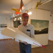 Eric Farnsworth holds one of the larger paper glider projects that was created for the Lawrence Paper Glider Fly-In workshop.