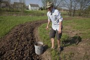 """Brady Karlin with All-N-1 Landscaping is pictured on his farm near a swale that is meant to trap rainwater and provide for a """"food forest"""" going in on the berm side."""
