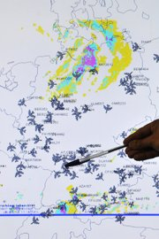 A member of the German Air Traffic Control center crisis management group points at a map showing the current air traffic in the sky Tuesday over Germany, in Langen, near Frankfurt, Germany.