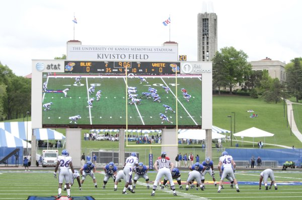 The Kansas Jayhawks get down at the line of scrimmage before the new wide-screen video board at Memorial Stadium.