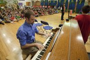 Daniel Musselman plays the piano to music he composed that was paired with poems written by Pinckney School students. Musselman and the students performed a selection of songs Thursday in front of a school assembly.
