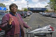 "Walmart employee Betty Dukes stands Wednesday in front of a Walmart in Pittsburgh, Calif. As a ""greeter,"" the cheerful Betty Dukes is one of the first employees customers usually see as they walk through the front doors of the Walmart store here, but the ordained Baptist minister also is the face of the largest gender bias class action lawsuit in U.S. history, Dukes v. Wal-Mart."