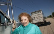 Valerie Foos, co-owner of Starving Artists Moving, is pictured with a couple of her moving trucks.